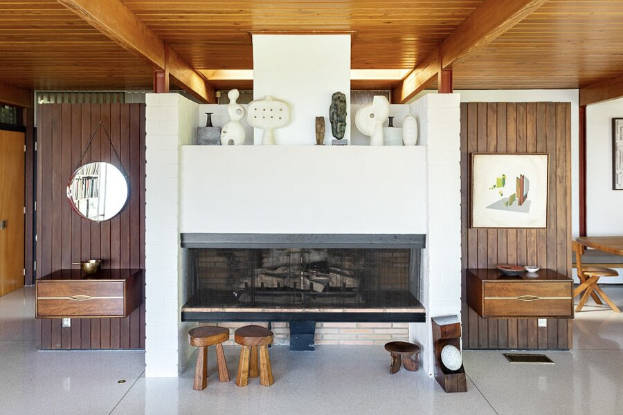 """The original fireplace features a brick surround, now partially painted white. Flanking both sides are Ellwood's wood-clad, """"floating walls""""—which can also be found in his Case Study House #16B that was built during the same year.  Photo 3 of 12 in An Impeccably Renovated Midcentury by Case Study Architect Craig Ellwood Asks $3.75M"""