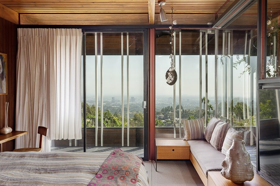 At the opposite end of the home, one of the three bedrooms benefits from a glazed corner. A new bench adds seating and storage near the window, while a sliding door provides access to a covered outdoor space with framed views of Los Angeles.  Photo 8 of 12 in An Impeccably Renovated Midcentury by Case Study Architect Craig Ellwood Asks $3.75M