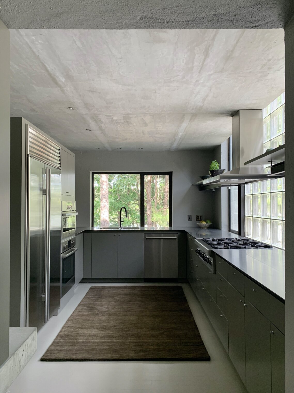 Behind the divider, the kitchen features Clark's original cabinetry and stainless steel countertops. The space also features updated appliances and a walk-in pantry.  Photo 6 of 12 in Surrounded by a Marshy Forest, This Fortress-Like Home Asks $1.7M in Virginia