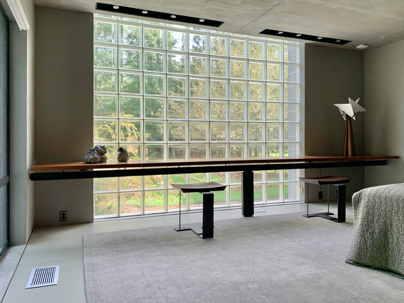 """One of the home's two bedrooms features a <span style=""""font-family: Theinhardt, -apple-system, BlinkMacSystemFont, &quot;Segoe UI&quot;, Roboto, Oxygen-Sans, Ubuntu, Cantarell, &quot;Helvetica Neue&quot;, sans-serif;"""">16-foot-long solid mahogany work station that is original to the home. Another glass-block window overlooks the yard.</span><span style=""""font-family: Theinhardt, -apple-system, BlinkMacSystemFont, &quot;Segoe UI&quot;, Roboto, Oxygen-Sans, Ubuntu, Cantarell, &quot;Helvetica Neue&quot;, sans-serif;""""> </span>  Photo 8 of 12 in Surrounded by a Marshy Forest, This Fortress-Like Home Asks $1.7M in Virginia"""