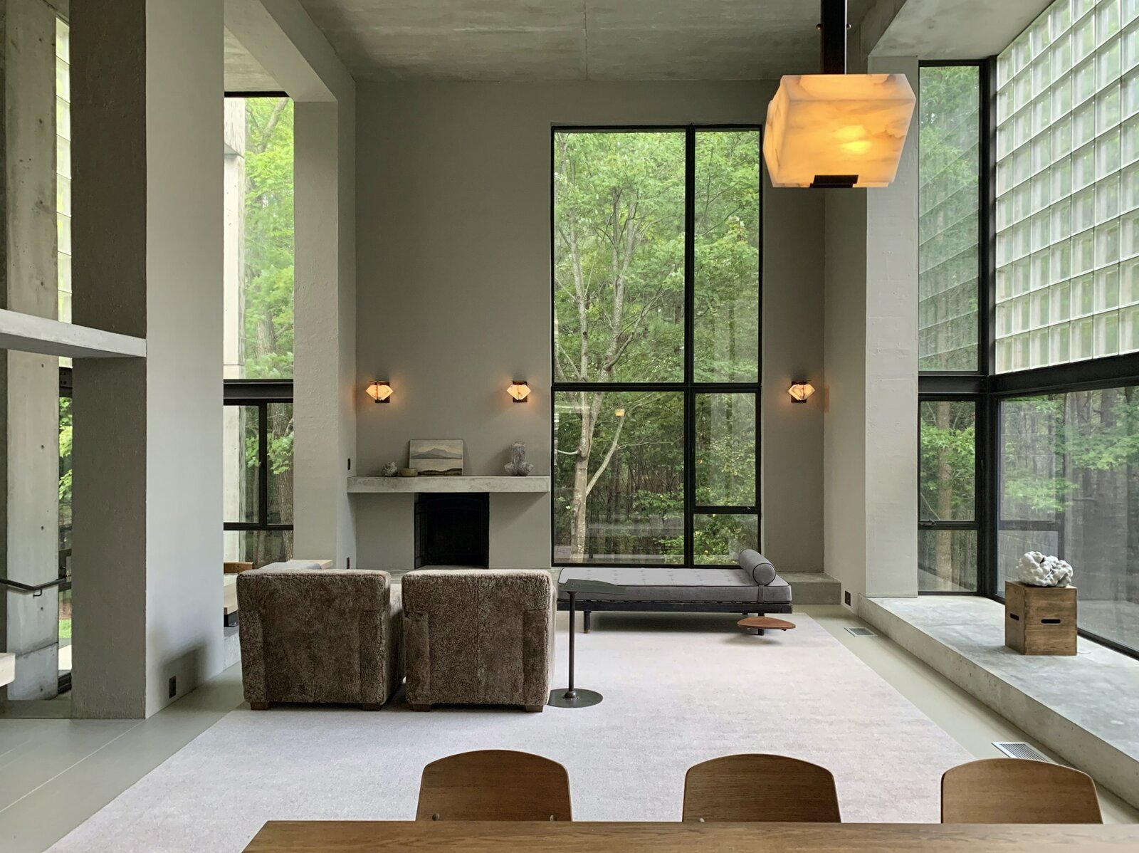 "A look back at the living area shows the massive windows that frame views of the forest. The space also features <span style=""font-family: Theinhardt, -apple-system, BlinkMacSystemFont, &quot;Segoe UI&quot;, Roboto, Oxygen-Sans, Ubuntu, Cantarell, &quot;Helvetica Neue&quot;, sans-serif;"">custom Pierre Chareau alabaster lighting and wood-burning fireplace.</span>  Photo 5 of 12 in Surrounded by a Marshy Forest, This Fortress-Like Home Asks $1.7M in Virginia"