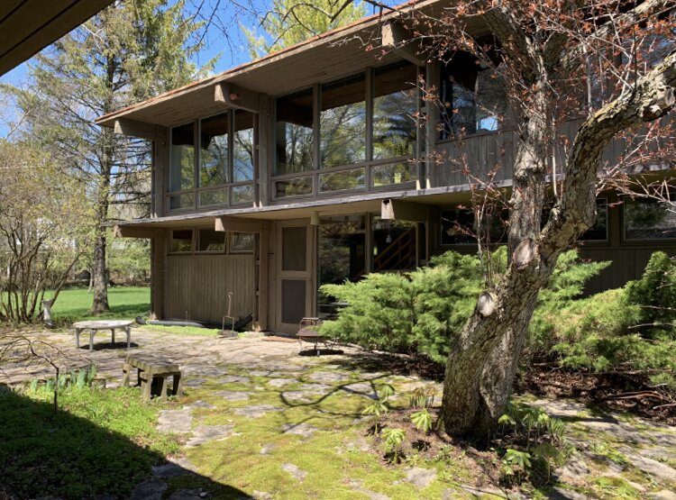 Before: An overgrown patio previously connected the two structures.  Photo 20 of 22 in Before & After: A Revived Midcentury in Wisconsin With Barrel-Vaulted Ceilings Asks $550K