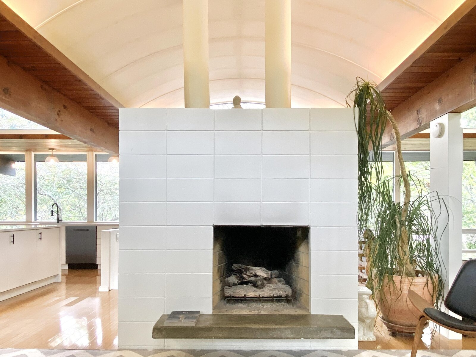 The updated fireplace, now painted white, retains the original floating hearth.  Photo 10 of 22 in Before & After: A Revived Midcentury in Wisconsin With Barrel-Vaulted Ceilings Asks $550K