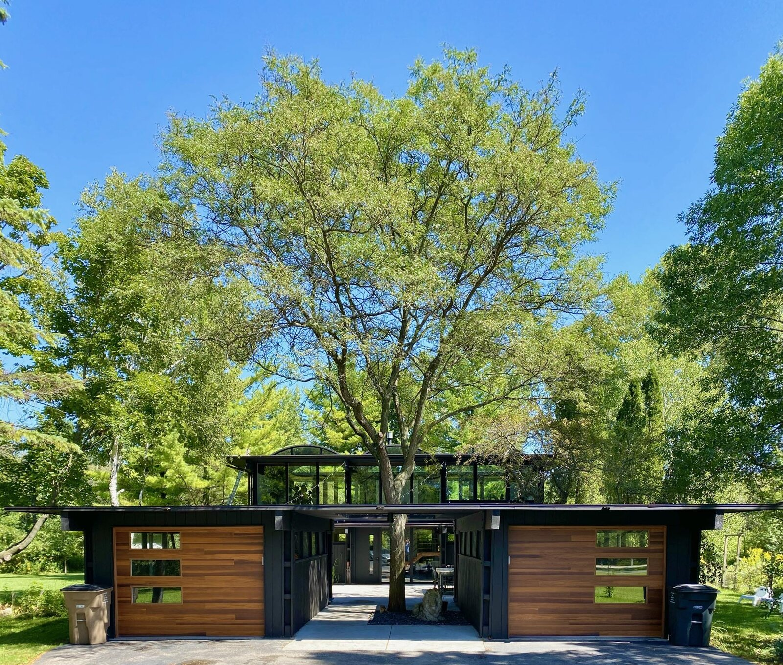 Recently listed in Bayside, Wisconsin, this renovated midcentury property comprises two detached structures—a two-bay garage and a barrel-vaulted house—connected by a central patio. A pass-through between the garages is punctuated by a large tree growing in the middle.  Photo 1 of 22 in Before & After: A Revived Midcentury in Wisconsin With Barrel-Vaulted Ceilings Asks $550K