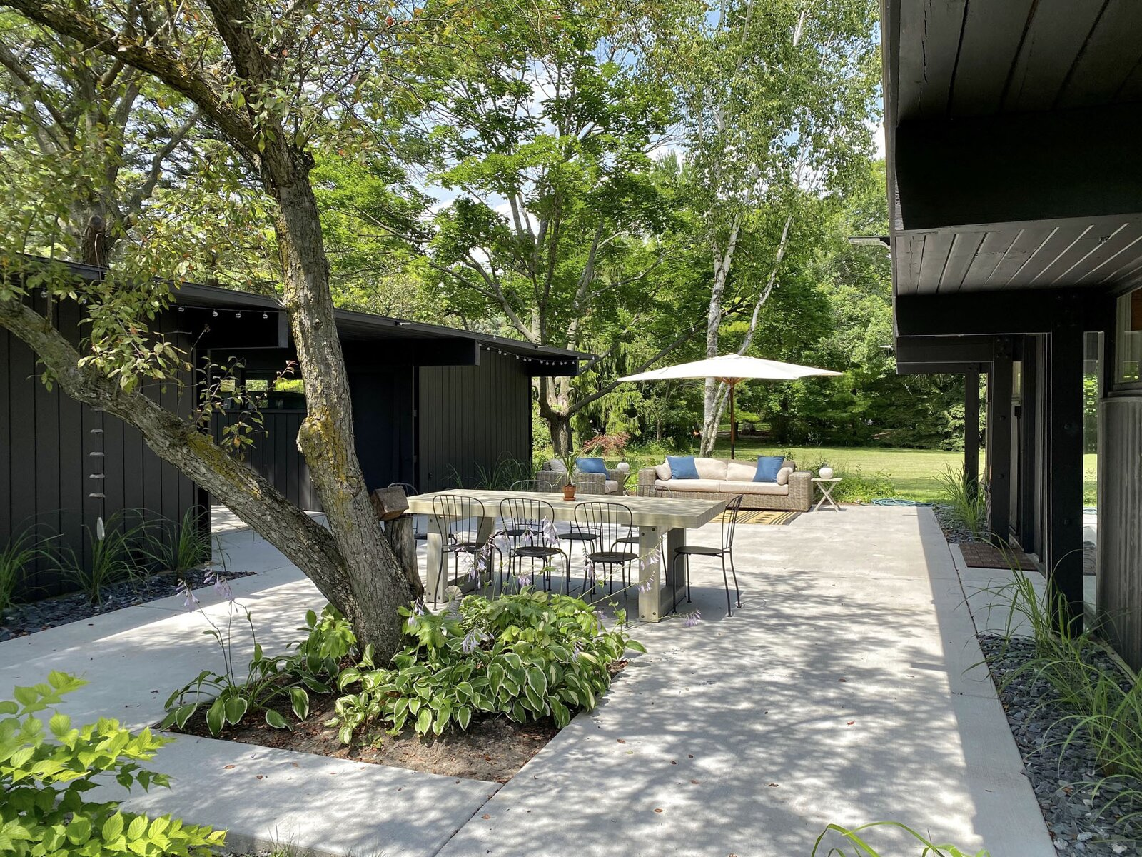 The new concrete patio provides a large, shaded area for entertaining.  Photo 21 of 22 in Before & After: A Revived Midcentury in Wisconsin With Barrel-Vaulted Ceilings Asks $550K