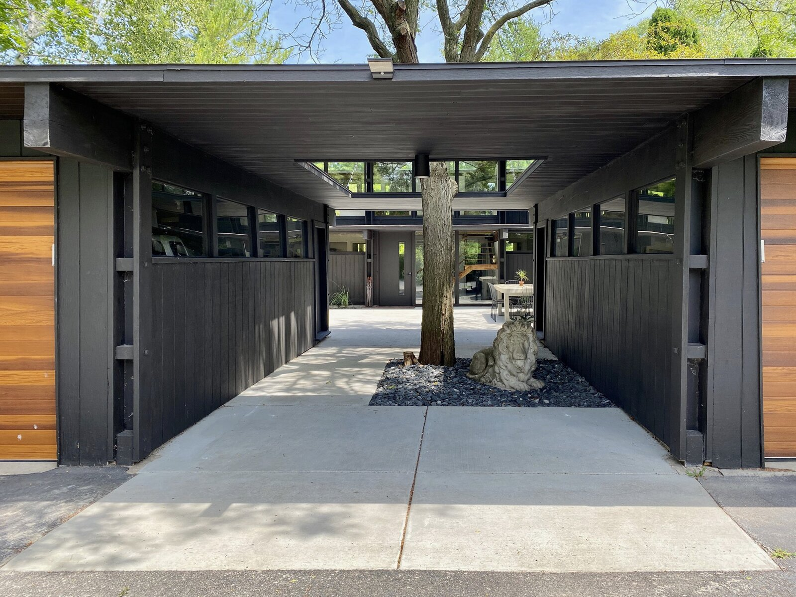 An original tree grows between the two garages, creating a serene entryway for the property.  Photo 22 of 22 in Before & After: A Revived Midcentury in Wisconsin With Barrel-Vaulted Ceilings Asks $550K