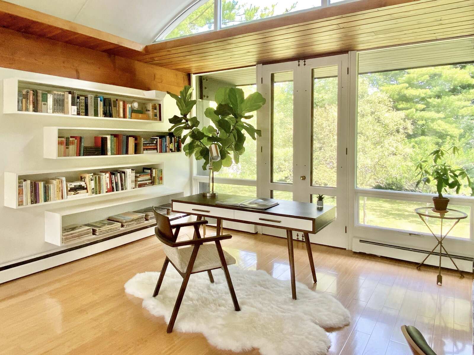 Today, one end of the living room is a sunny office space with built-in floating shelves.  Photo 12 of 22 in Before & After: A Revived Midcentury in Wisconsin With Barrel-Vaulted Ceilings Asks $550K