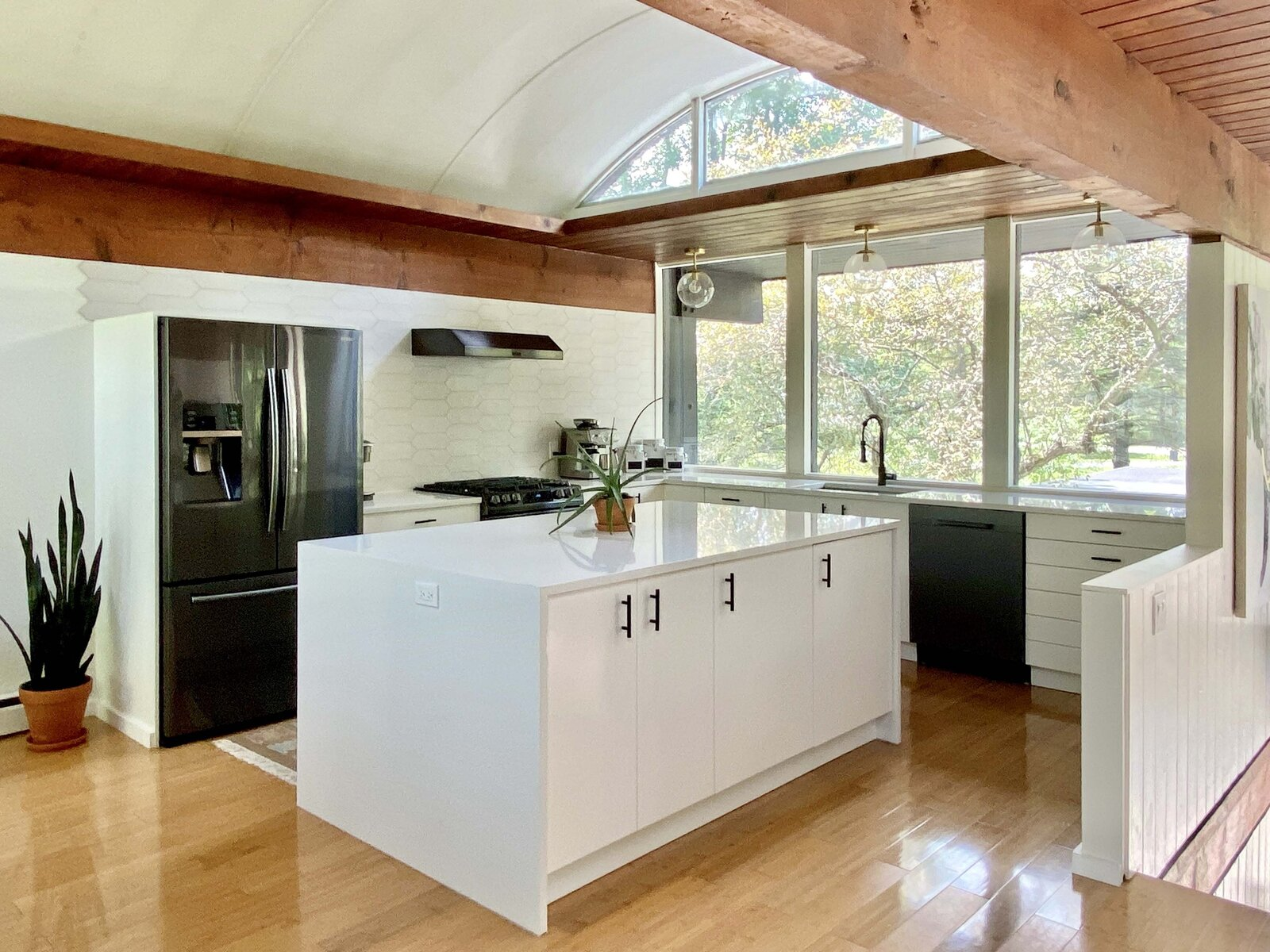 With the previous wall removed, the updated kitchen makes room for a central island overlooking the dining area and staircase landing. The same full-width window overlooks the front of the home and the central patio.  Photo 5 of 22 in Before & After: A Revived Midcentury in Wisconsin With Barrel-Vaulted Ceilings Asks $550K