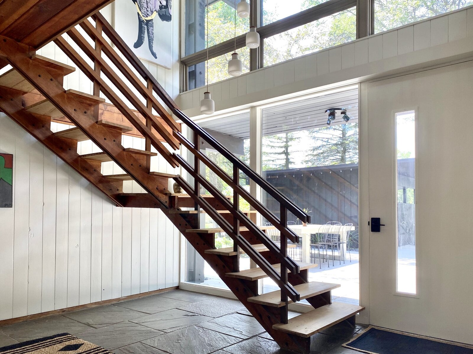 The staircase also provides access to the main entrance, as well as the bedrooms.  Photo 15 of 22 in Before & After: A Revived Midcentury in Wisconsin With Barrel-Vaulted Ceilings Asks $550K