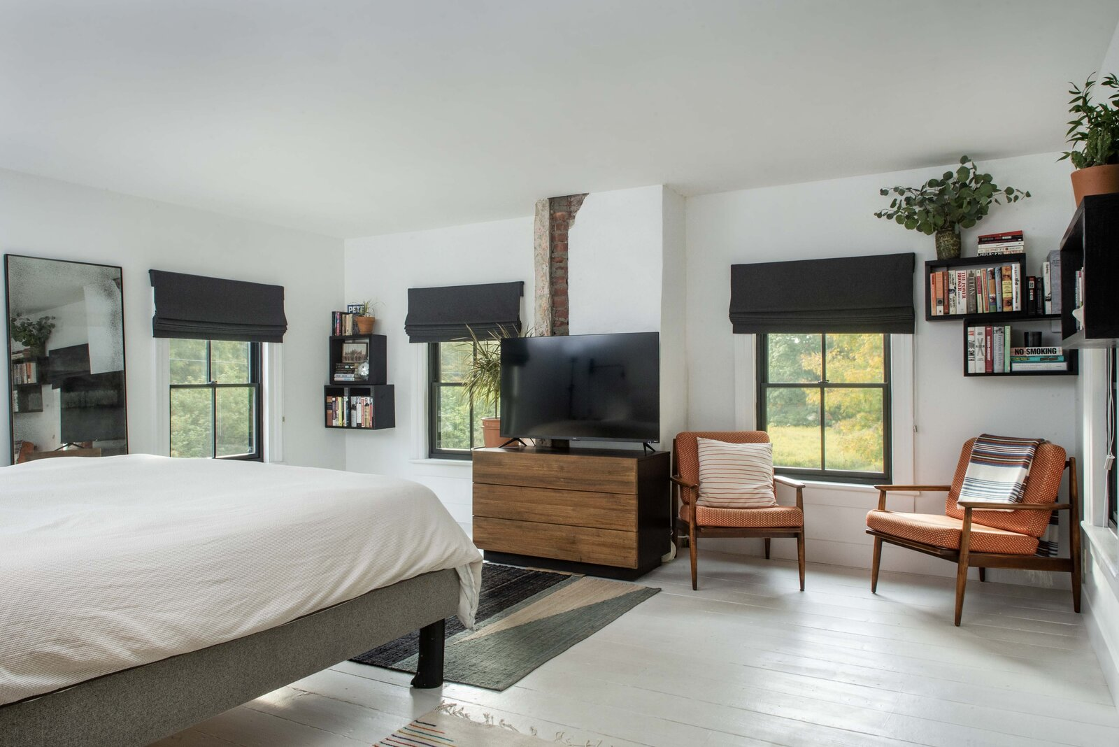 Here, the sunlit principal bedroom benefits from windows along three sides and also features exposed brick along an original chimney wall.  Photo 11 of 14 in For $795K, This 1865 Greek Revival Farmhouse Could Be Your Escape From New York