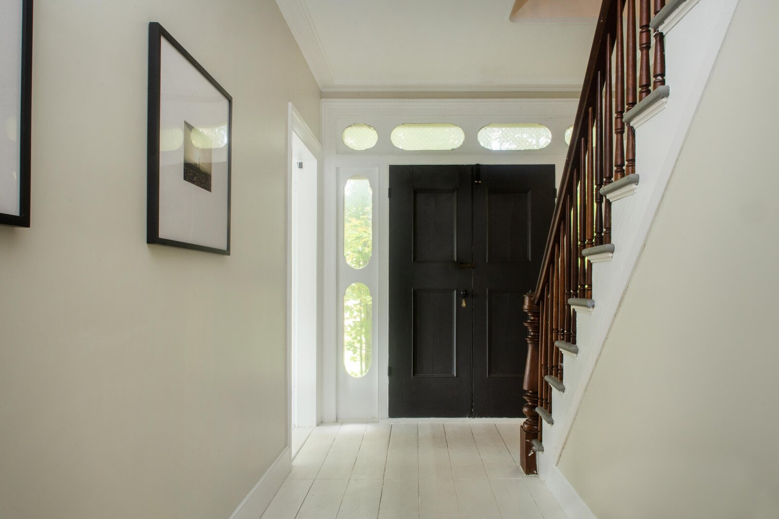 A traditional foyer and central staircase are located between the living and dining rooms.  Photo 3 of 14 in For $795K, This 1865 Greek Revival Farmhouse Could Be Your Escape From New York