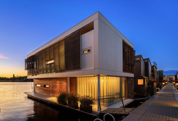 Completed in 2016, this contemporary floating home on Seattle's Lake Union was recently listed for sale. At nighttime, illuminated panels of channel glass define a corner of the facade, which is also clad in teak slats and low-maintenance ceramic panels.
