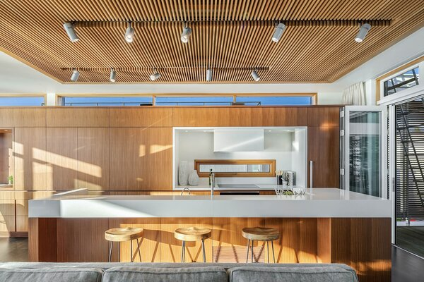 A wall of afromosia cabinetry runs along one side of the upper level, providing ample storage for both the kitchen and dining area. Wood slats define the ceiling above the kitchen island and adjacent living area, while folding glass doors open onto the terraces.