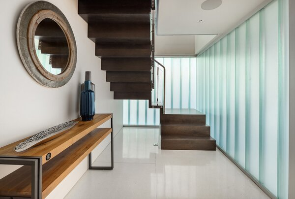 The translucent channel glass illuminates the entryway with an abundance of natural light. A cantilevered staircase leads up to the living areas, while a hallway (not pictured) leads to the home's bedrooms on this level.