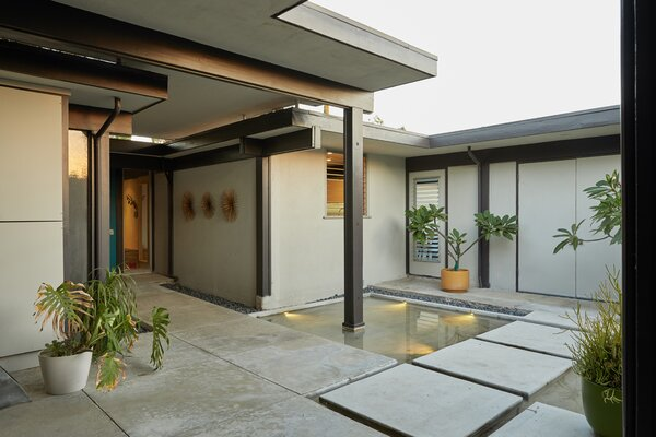 From the driveway, double doors open onto a serene courtyard complete with reflecting pools and pathways leading to the main house (left), as well as a separate studio (right).