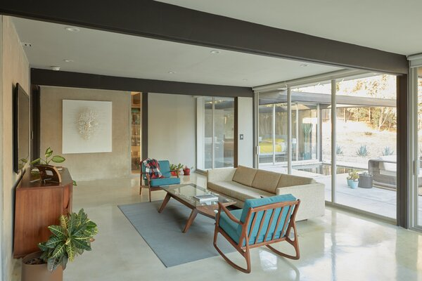 A large living area stretches across the rear of the main house, illuminated by natural light from multiple sliding glass doors. Original concrete walls divide the space.