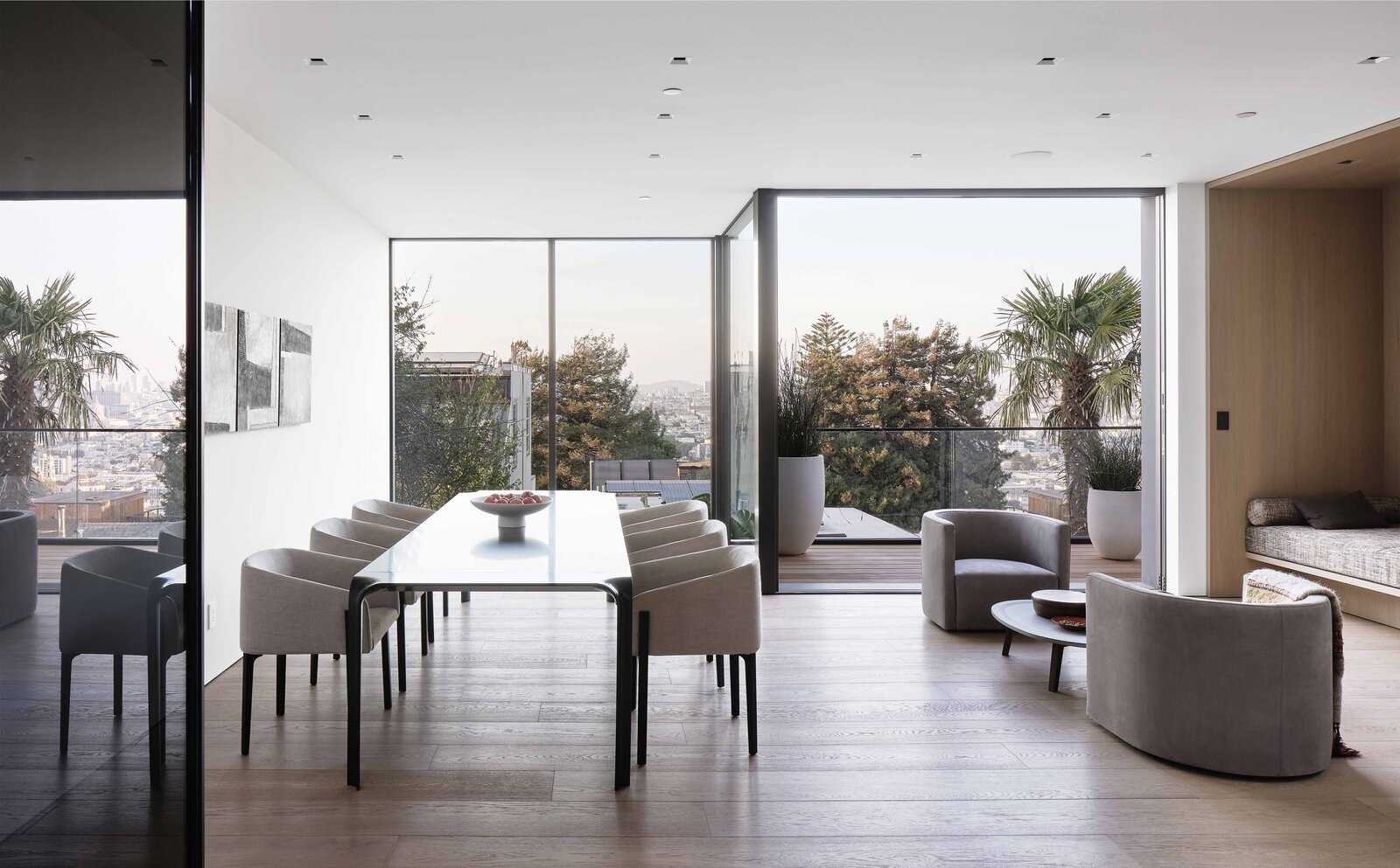 Another view of the dining and seating area show the full-height windows across the rear of the home, through which distant views of the city are visible.  Photo 4 of 19 in This Radiant San Francisco Residence Hits the Market at $6.8M
