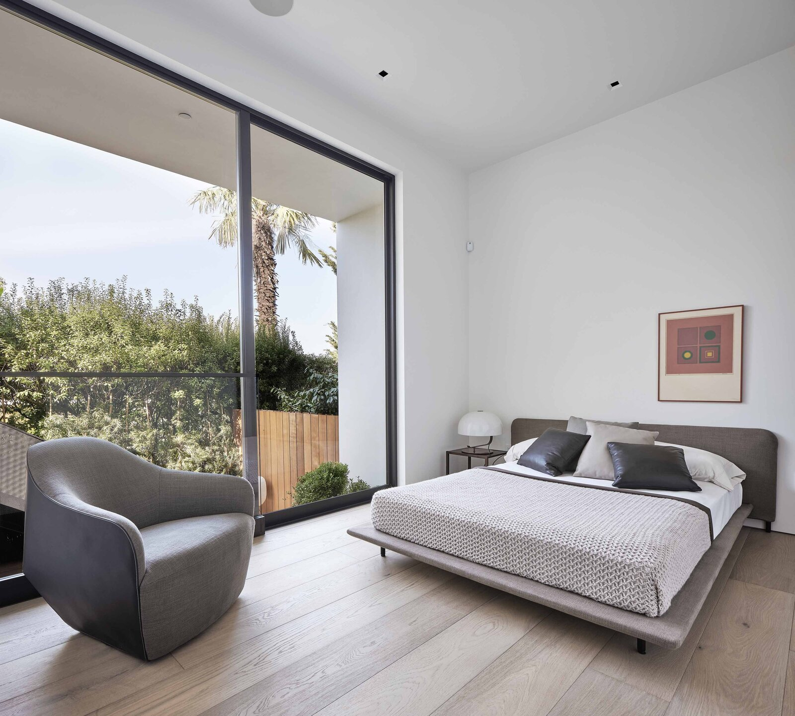 At the opposite end of the ground level, both of the secondary bedrooms overlooks a sunken patio and deck in the backyard.  Photo 13 of 19 in This Radiant San Francisco Residence Hits the Market at $6.8M