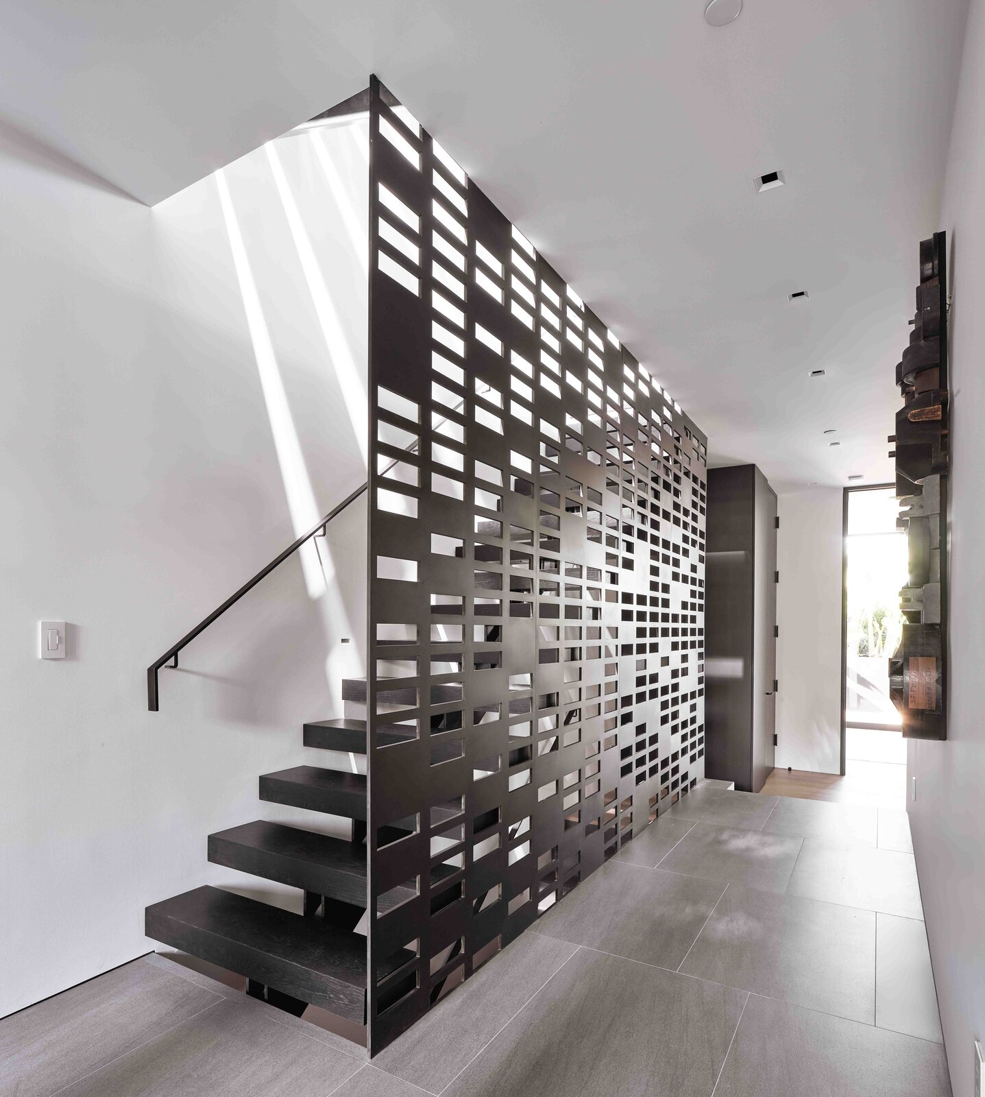 """Inside the entryway, a custom steel staircase and screen by <span style=""""font-family: Theinhardt, -apple-system, BlinkMacSystemFont, &quot;Segoe UI&quot;, Roboto, Oxygen-Sans, Ubuntu, Cantarell, &quot;Helvetica Neue&quot;, sans-serif;"""">Melissa MacDonald Metalworks filters natural light from the skylight above. The home's inverted floor plan places each of the three bedrooms on the ground floor and the main living areas upstairs.</span>  Photo 2 of 19 in This Radiant San Francisco Residence Hits the Market at $6.8M"""