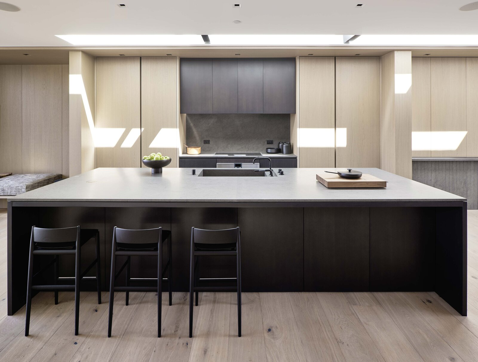 The streamlined kitchen cabinetry is accented by Gaggenau appliances and Basaltina stone countertops. Another skylight runs above the kitchen.  Photo 8 of 19 in This Radiant San Francisco Residence Hits the Market at $6.8M