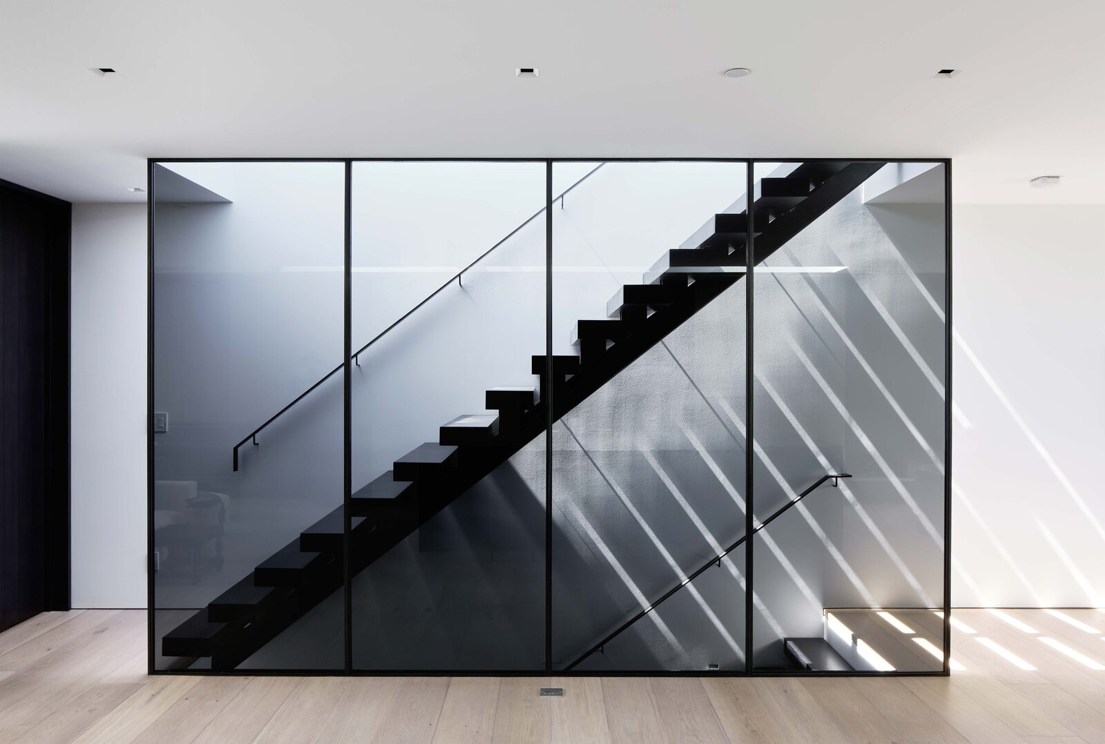 Stairs in the kitchen lead up to a motorized skylight and the roof. Both the staircase design and an adjacent screen filter natural light entering from above.  Photo 7 of 19 in This Radiant San Francisco Residence Hits the Market at $6.8M
