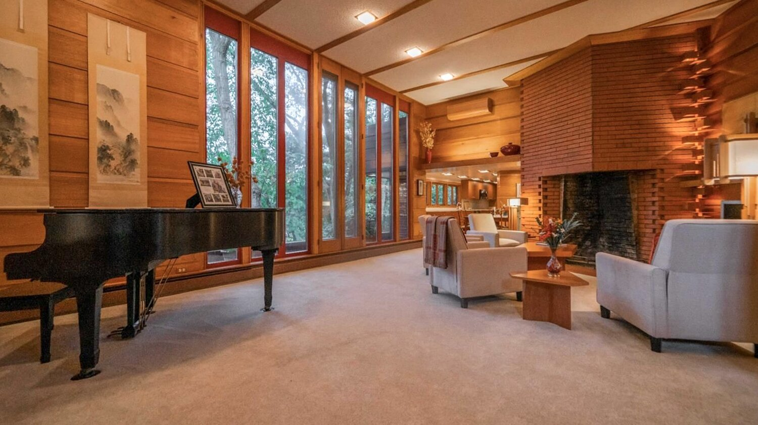 Throughout the interior, original wood-clad walls flank a brick fireplace finished in an interlocking and extruding pattern. Large windows also overlook the wooded lot.  Photo 2 of 11 in Frank Lloyd Wright's Dune House Hits the Market for $1.2M