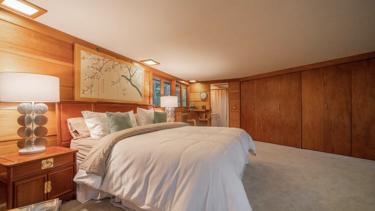 A large principal suite is located along the top level of the home. The space features board-and-batten walls, along with access to an outdoor area.  Photo 8 of 11 in Frank Lloyd Wright's Dune House Hits the Market for $1.2M