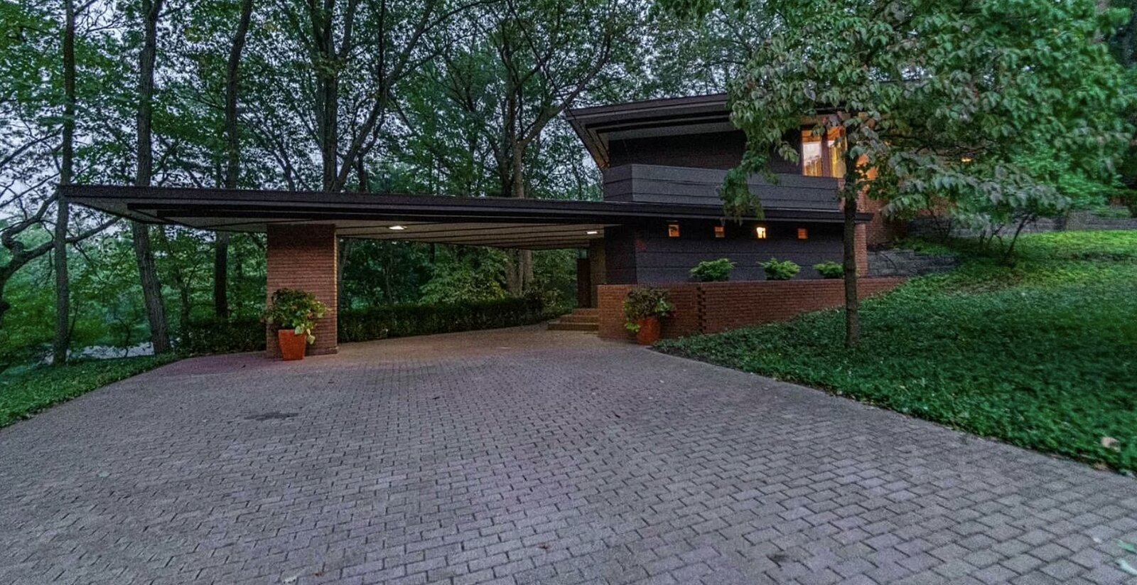 One end of the home features the original, Wright-designed carport and entryway, while the opposite end offers an additional parking area and a two-car garage, also added by Howe.  Photo 11 of 11 in Frank Lloyd Wright's Dune House Hits the Market for $1.2M
