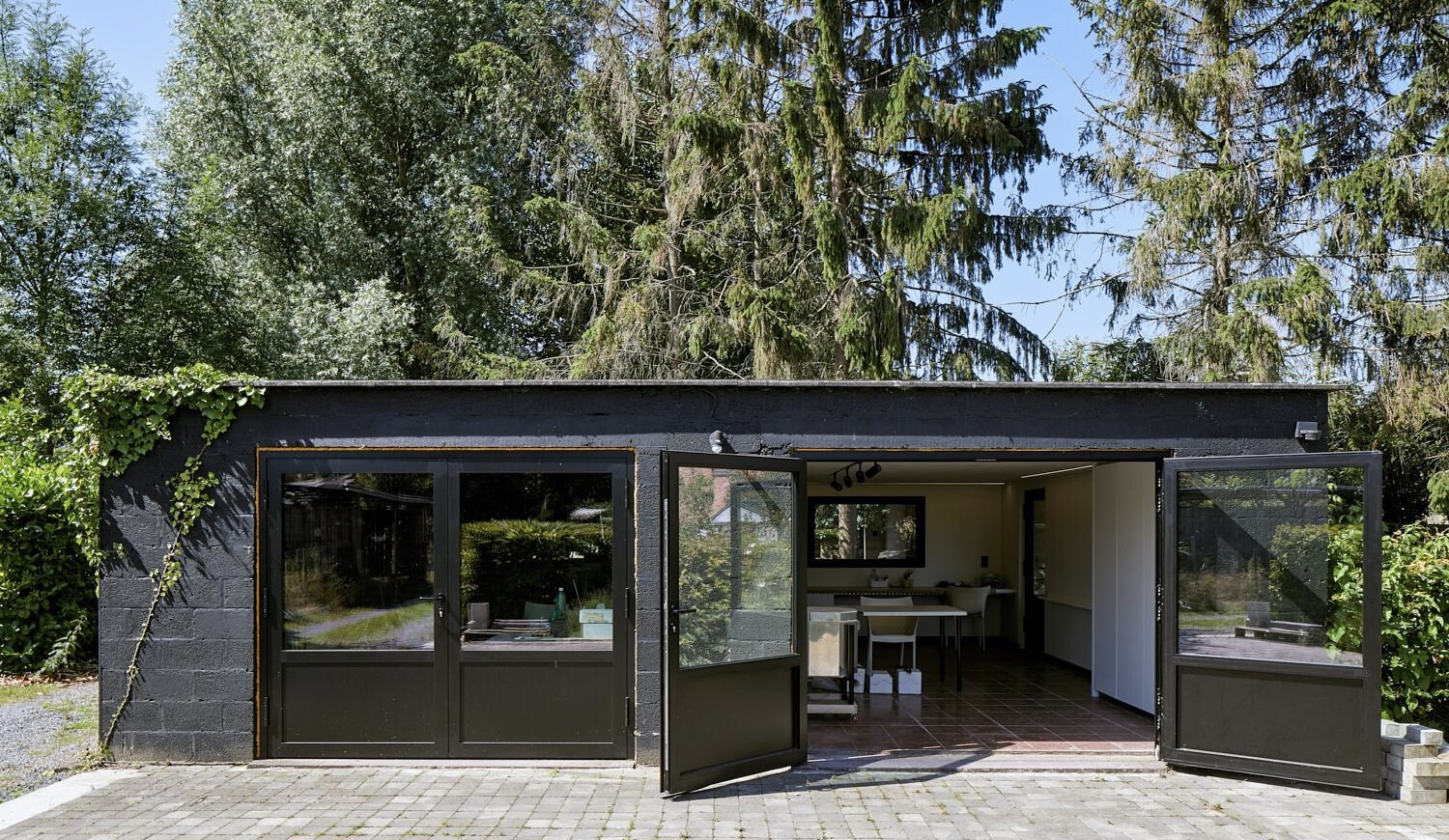 One section of the two-car garage is currently used as a studio and workspace. Glass doors open the room up to sunlight and fresh air.  Photo 14 of 17 in For €795K, You Can Buy This Boxy Belgian Home With a Surprisingly Colorful Interior