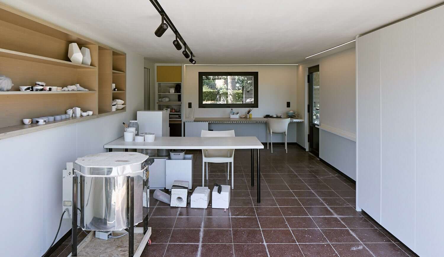 Inside, built-in shelving and cabinetry offer many opportunities for using the garage space.  Photo 15 of 17 in For €795K, You Can Buy This Boxy Belgian Home With a Surprisingly Colorful Interior
