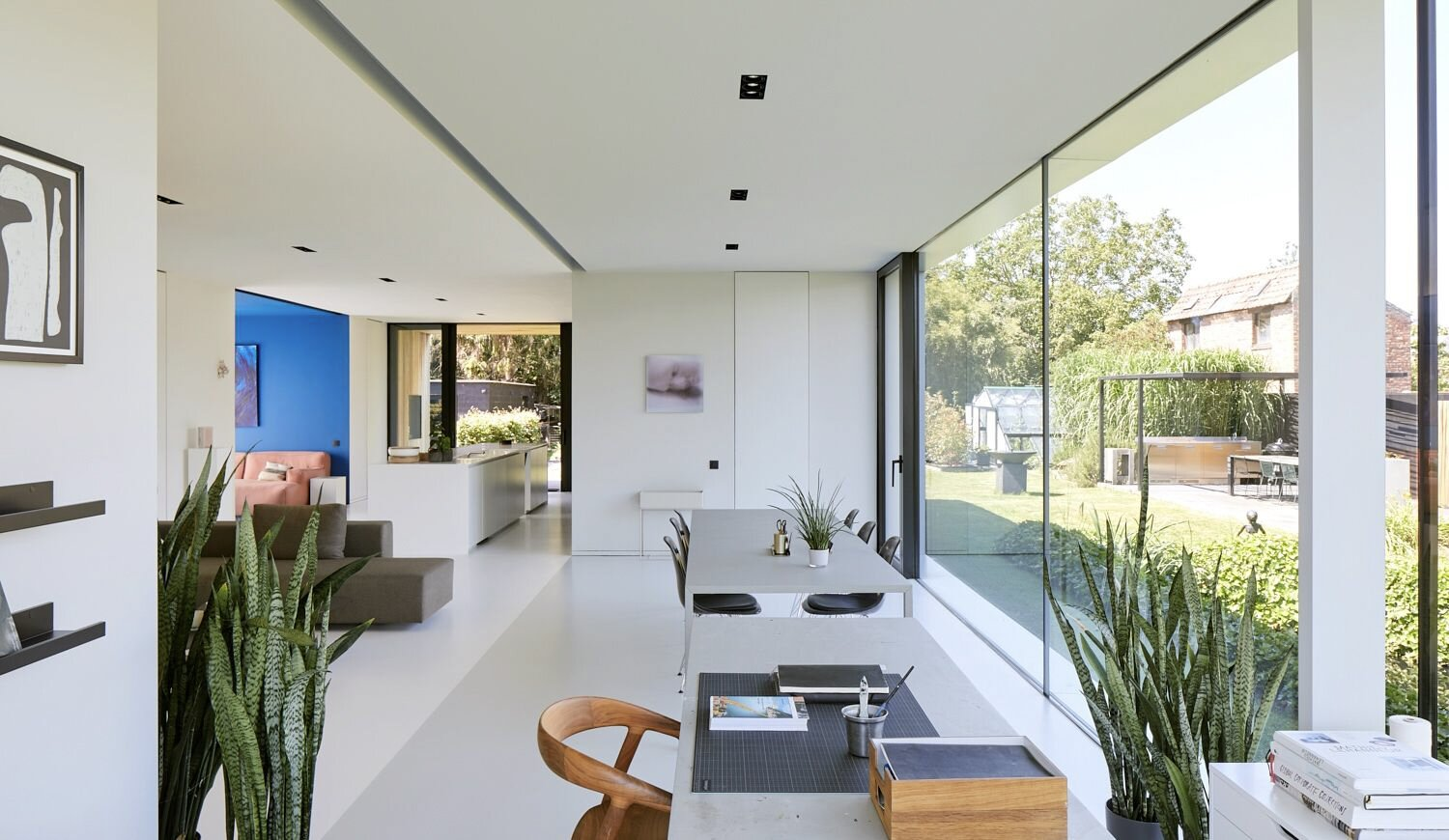 The glazed wall overlooks a backyard garden, which can also be accessed directly by a door near the dining area.  Photo 8 of 17 in For €795K, You Can Buy This Boxy Belgian Home With a Surprisingly Colorful Interior