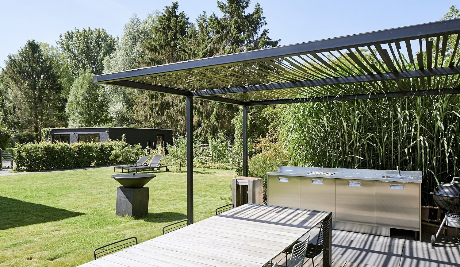 Situated in a rear corner of the lot, the partially covered patio comes with a large space for dining and an outdoor kitchen.  Photo 13 of 17 in For €795K, You Can Buy This Boxy Belgian Home With a Surprisingly Colorful Interior