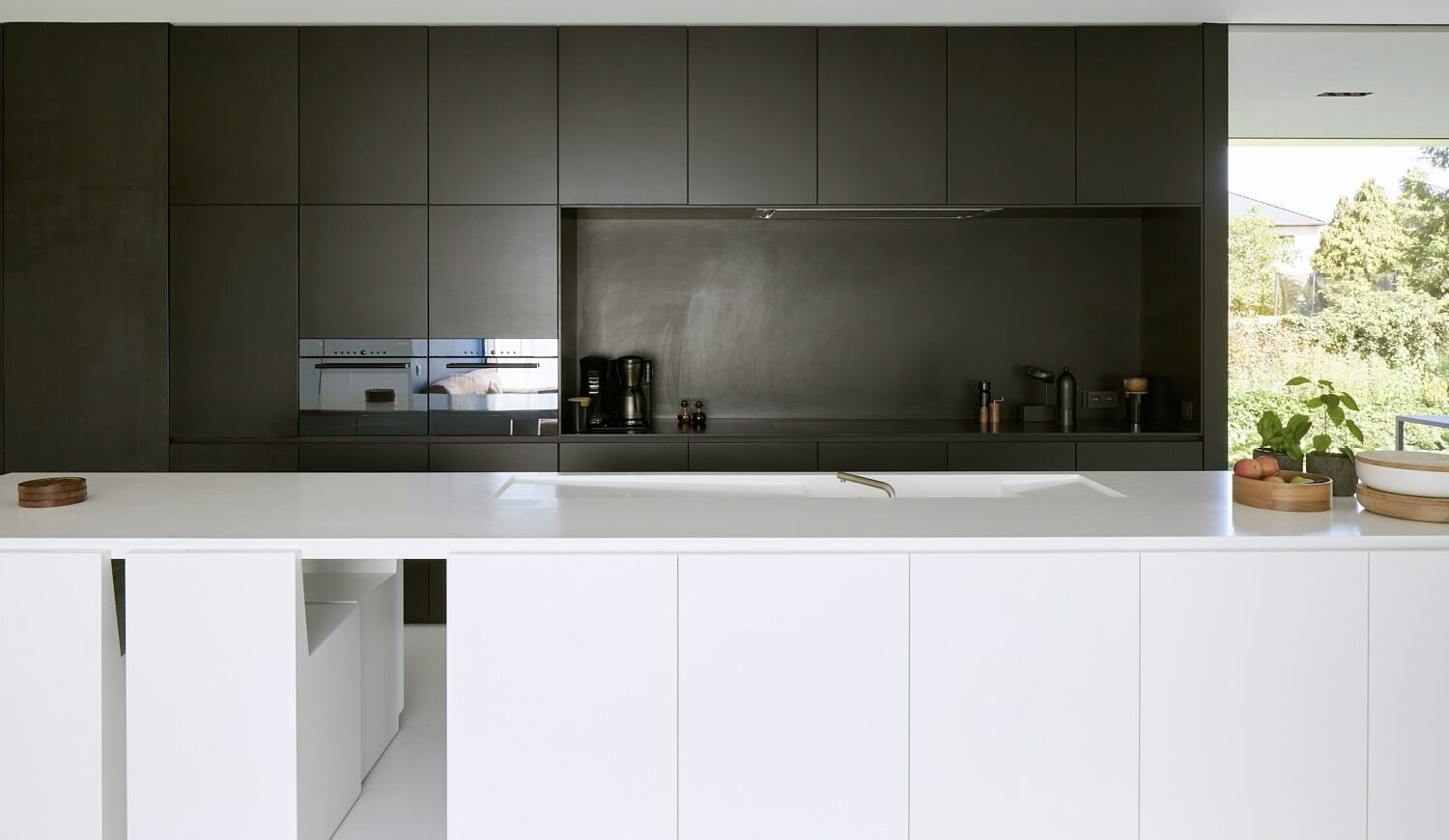 The kitchen features a matte-black wall of cabinetry contrasted by an all-white central island. Matching chairs, custom designed by the architect, provide built-in seating.  Photo 5 of 17 in For €795K, You Can Buy This Boxy Belgian Home With a Surprisingly Colorful Interior