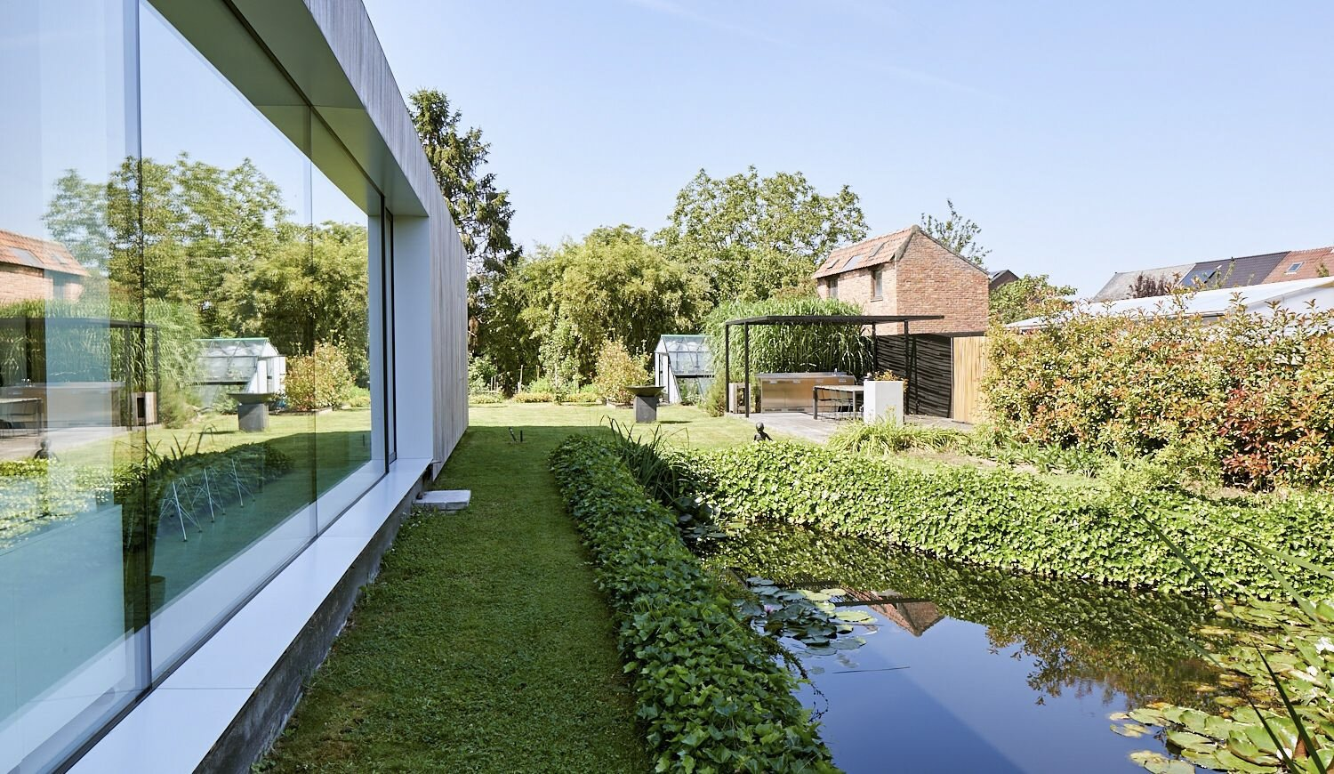 A small pond makes a charming addition to the side yard.  Photo 12 of 17 in For €795K, You Can Buy This Boxy Belgian Home With a Surprisingly Colorful Interior