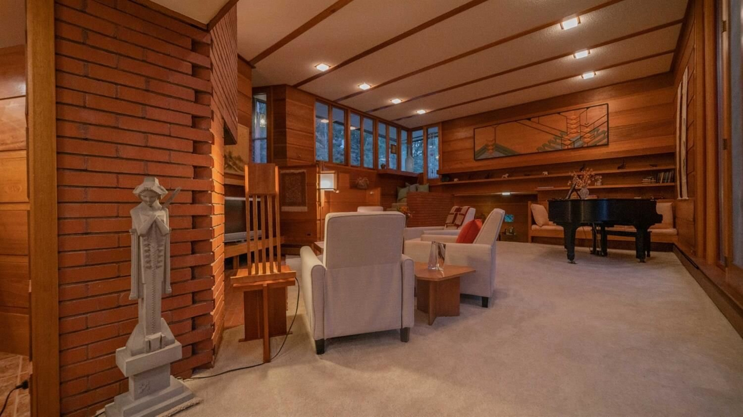 Another view of the living area shows the built-in shelves and bench along the rear wall. One of the home's owners, John Peterson, reportedly built some of the furnishings by following Wright's plans.  Photo 5 of 11 in Frank Lloyd Wright's Dune House Hits the Market for $1.2M
