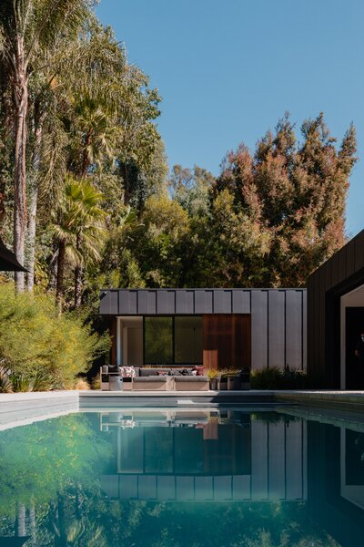 The Laurel Hills Residence and the surrounding palm trees reflect on the surface of the 40-foot-long swimming pool.