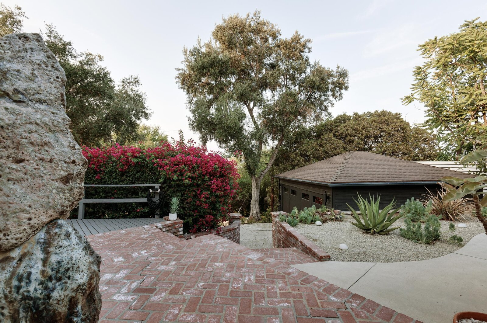 A view from the main entrance and the upper terrace reveal a paved walkway that leads down to the two-car garage.  Photo 14 of 16 in Listed at $950K, This Clean-Lined Cottage in Los Angeles Is a Fresh Take on City Living