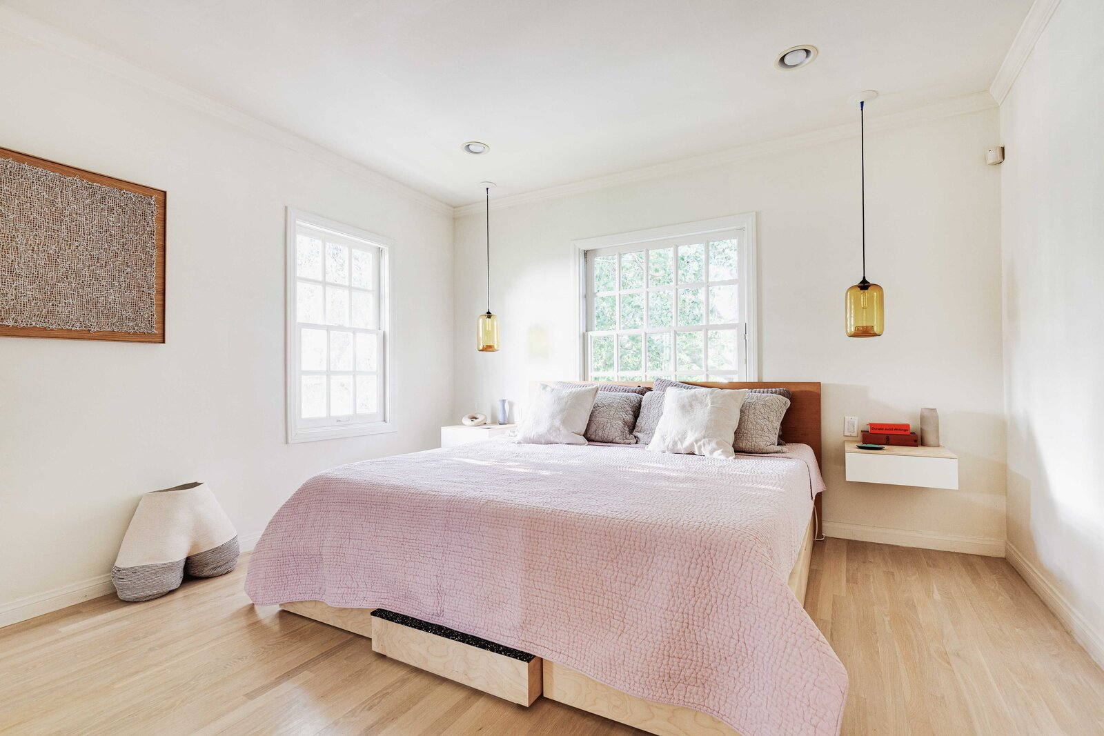 The primary bedroom sits in a corner of the home and receives natural light from two windows.  Photo 9 of 16 in Listed at $950K, This Clean-Lined Cottage in Los Angeles Is a Fresh Take on City Living