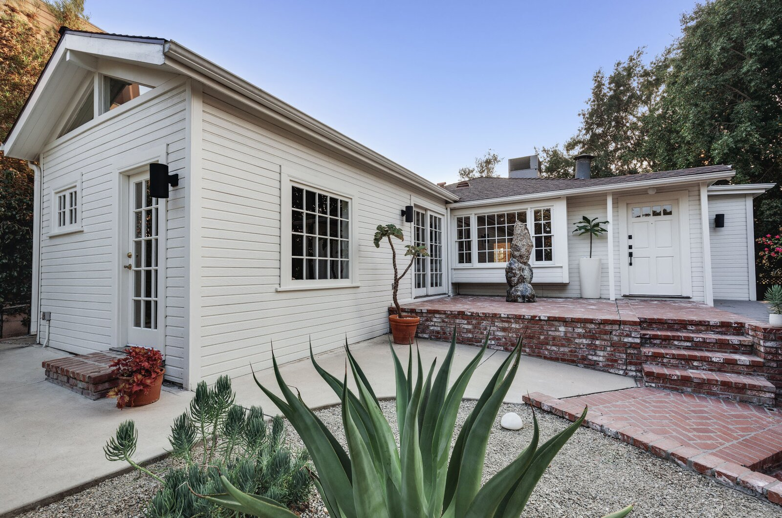 Recently listed in the Glassell Park neighborhood of Los Angeles, this renovated and expanded 1940s cottage sits on an elevated lot above other homes on the street. Multiple patios surround the L-shaped structure, providing a welcoming entrance.  Photo 1 of 16 in Listed at $950K, This Clean-Lined Cottage in Los Angeles Is a Fresh Take on City Living