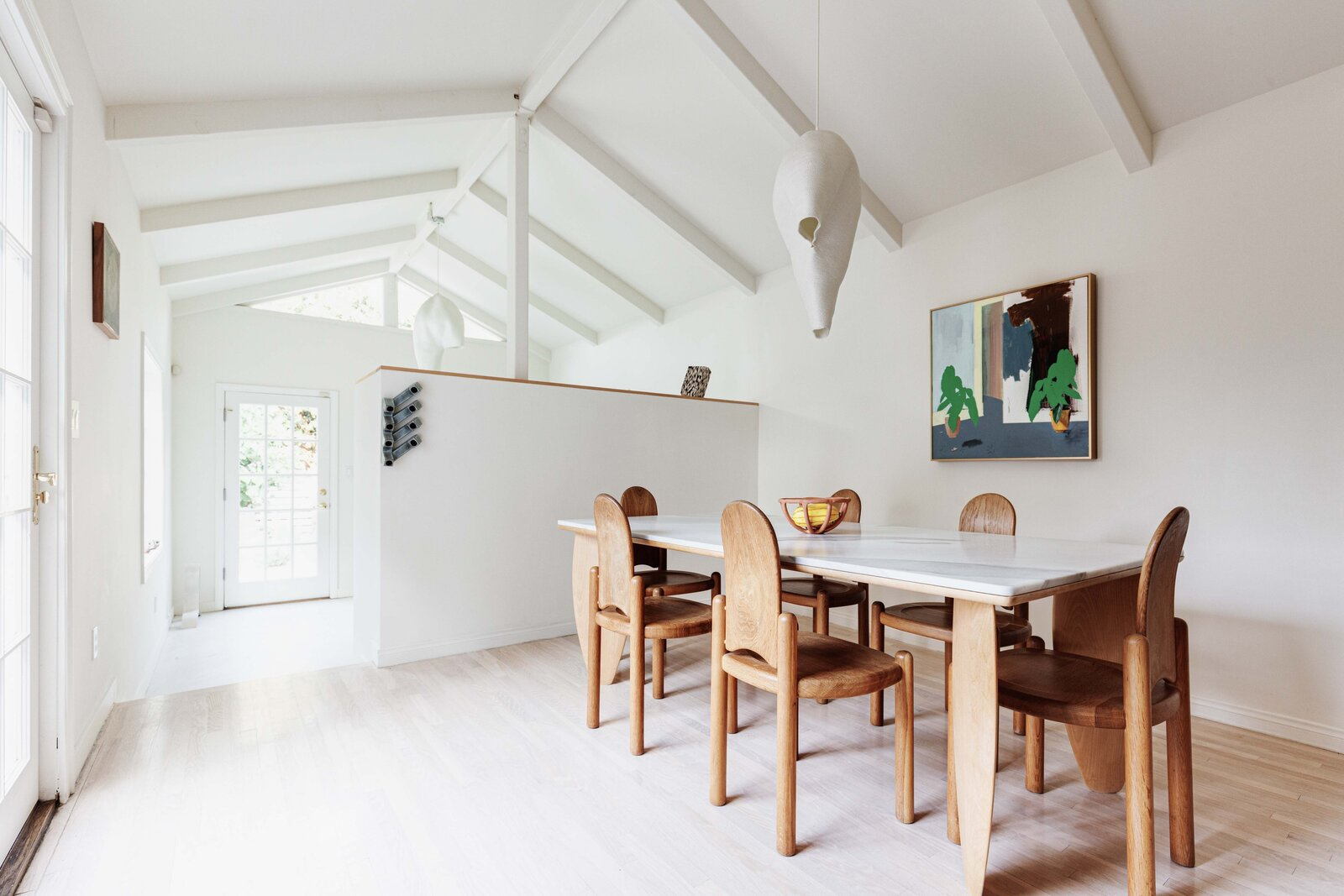 A vaulted ceiling with exposed beams creates an airy atmosphere for the dining area while French doors provide direct access to the patio.  Photo 7 of 16 in Listed at $950K, This Clean-Lined Cottage in Los Angeles Is a Fresh Take on City Living