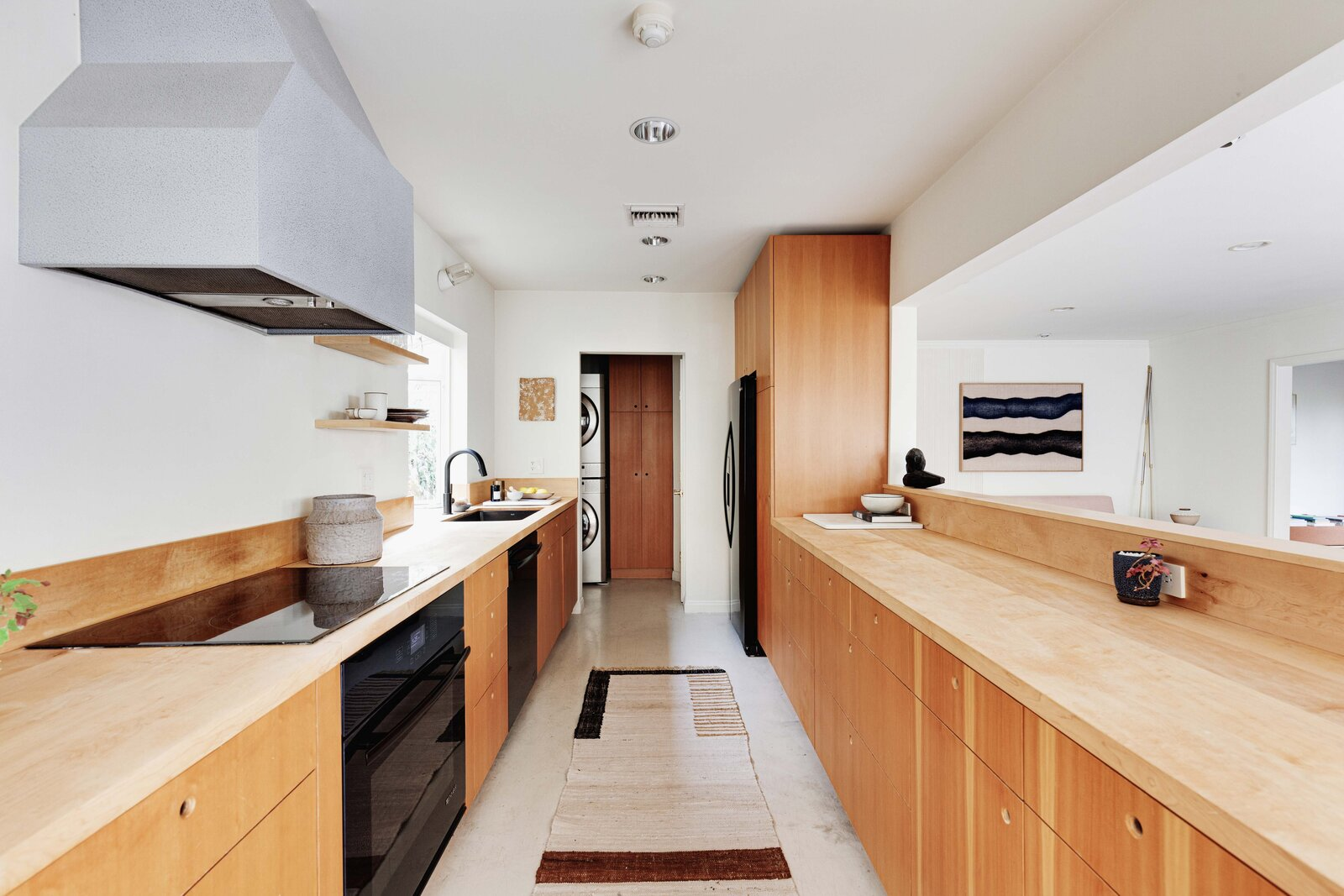 On the opposite side of the home, a galley-style kitchen features a large pass-through connecting to the living room. Handmade wood cabinetry, open shelving, and updated appliances round out the space.  Photo 5 of 16 in Listed at $950K, This Clean-Lined Cottage in Los Angeles Is a Fresh Take on City Living