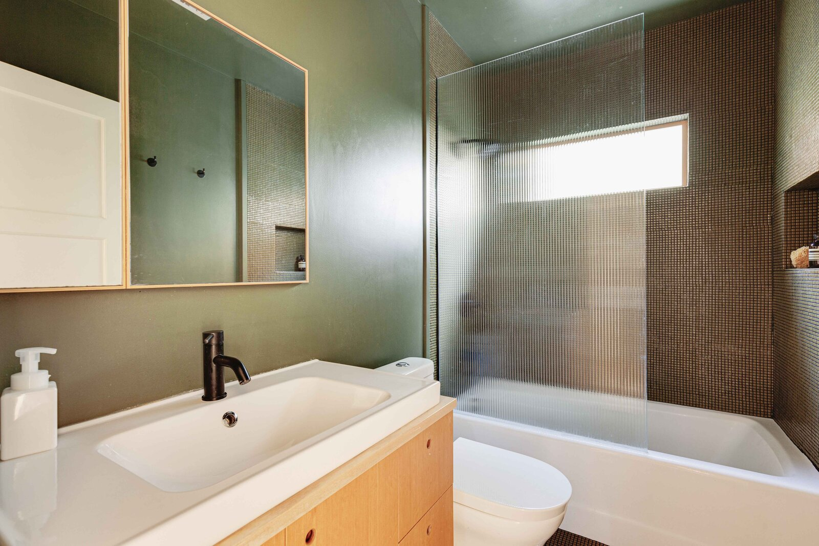 The home's only full bathroom offers handmade cabinetry, as well as updated finishes.  Photo 10 of 16 in Listed at $950K, This Clean-Lined Cottage in Los Angeles Is a Fresh Take on City Living
