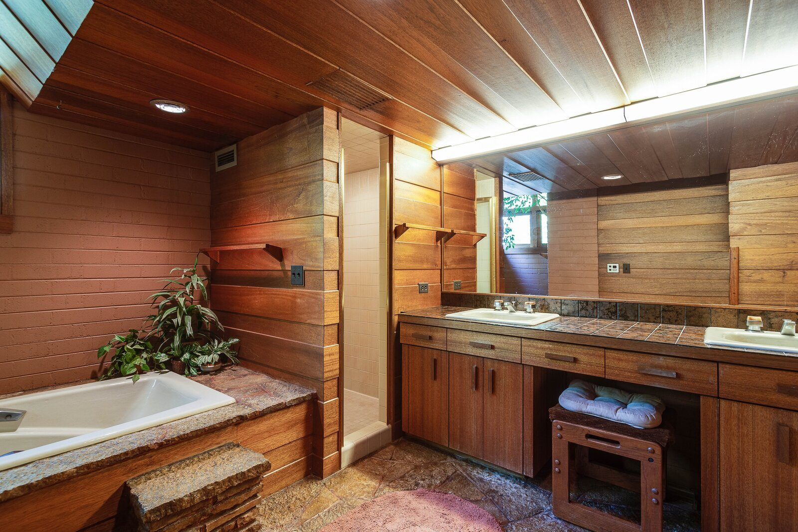 The adjacent bathroom continues the material palette of flagstone, mahogany, and brick.  Photo 12 of 17 in For the First Time Ever, This Winsome Illinois Home by Frank Lloyd Wright Is on the Market