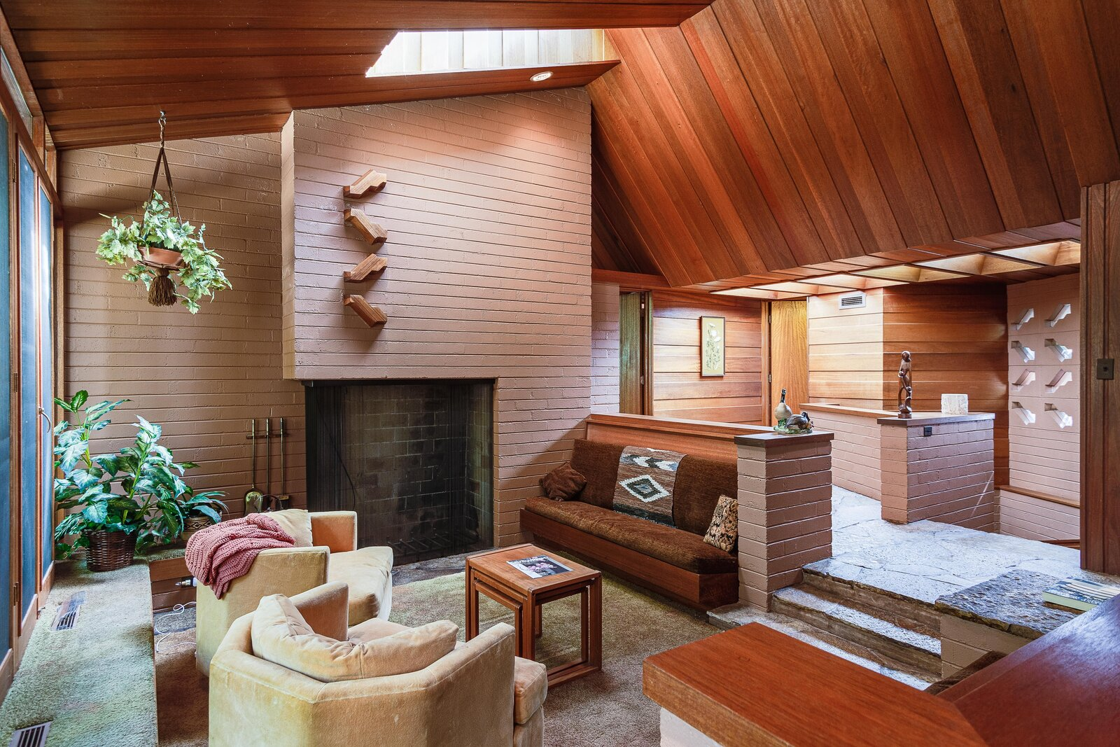 A sunken conversation area is located just off of the entrance. Decoratively hanging above the fireplace are mahogany blocks that Busche and his team used to replicate Wright's original block design throughout the new additions.  Photo 3 of 17 in For the First Time Ever, This Winsome Illinois Home by Frank Lloyd Wright Is on the Market