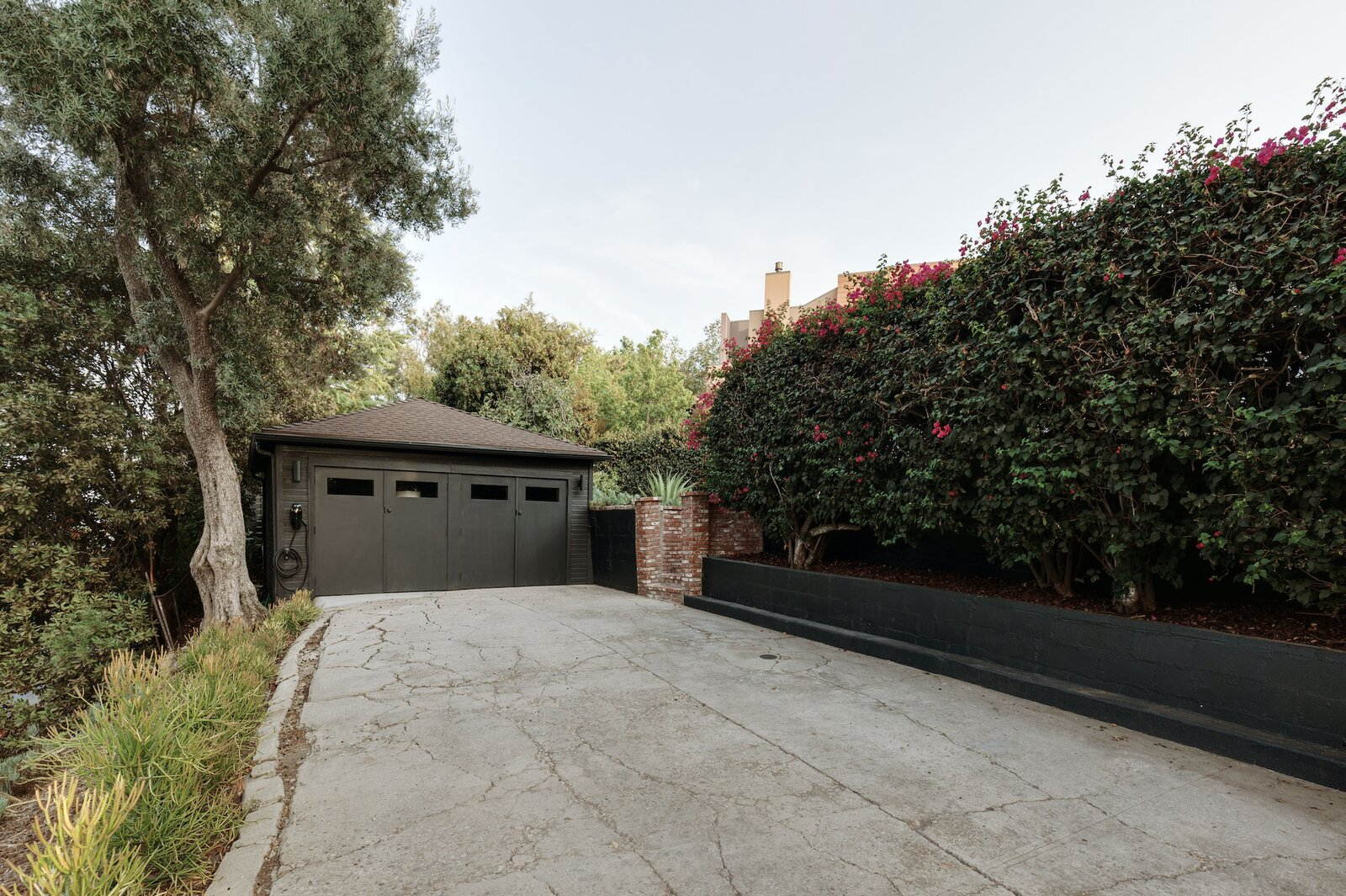 In addition to the garage, a long, gated driveway provides ample space for parking.  Photo 16 of 16 in Listed at $950K, This Clean-Lined Cottage in Los Angeles Is a Fresh Take on City Living