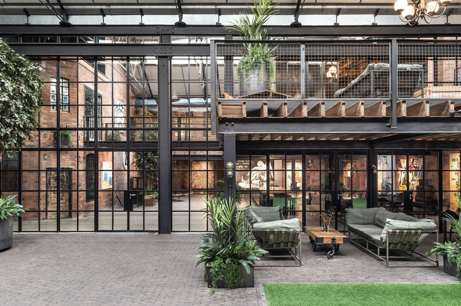 """The triple-height central courtyard is enclosed on one side by a wall of steel-framed Crittal windows and doors. A multi-level seating area connects to both public and private spaces.  Photo 4 of 15 in This Live/Work Warehouse That Starred in Steven Spielberg's """"Ready Player One"""" Lists for £2.75M"""
