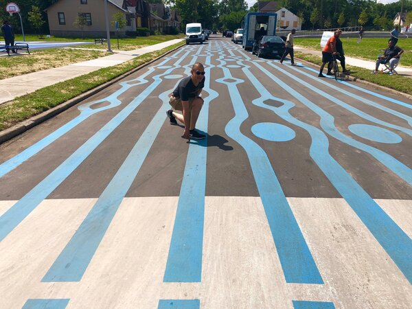 Steven Lewis poses by colorful markings on a street in detroit, designed to slow down drivers, and make them conscious of their surroundings.