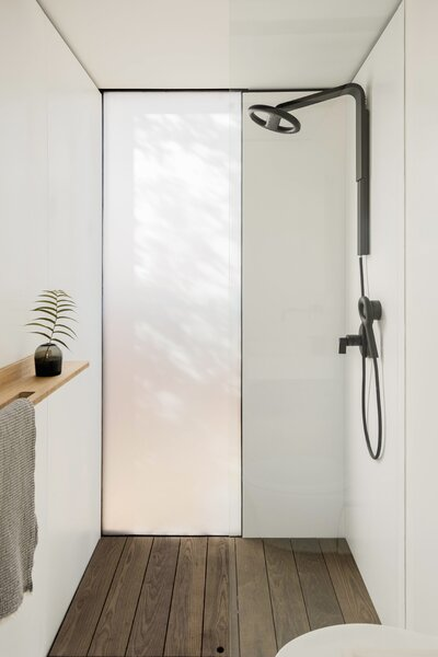 In the bathroom, glass divides the shower area and toilet for an open feel. The low-flow shower head by Nebia cuts water use by 65% compared to a traditional fixture.