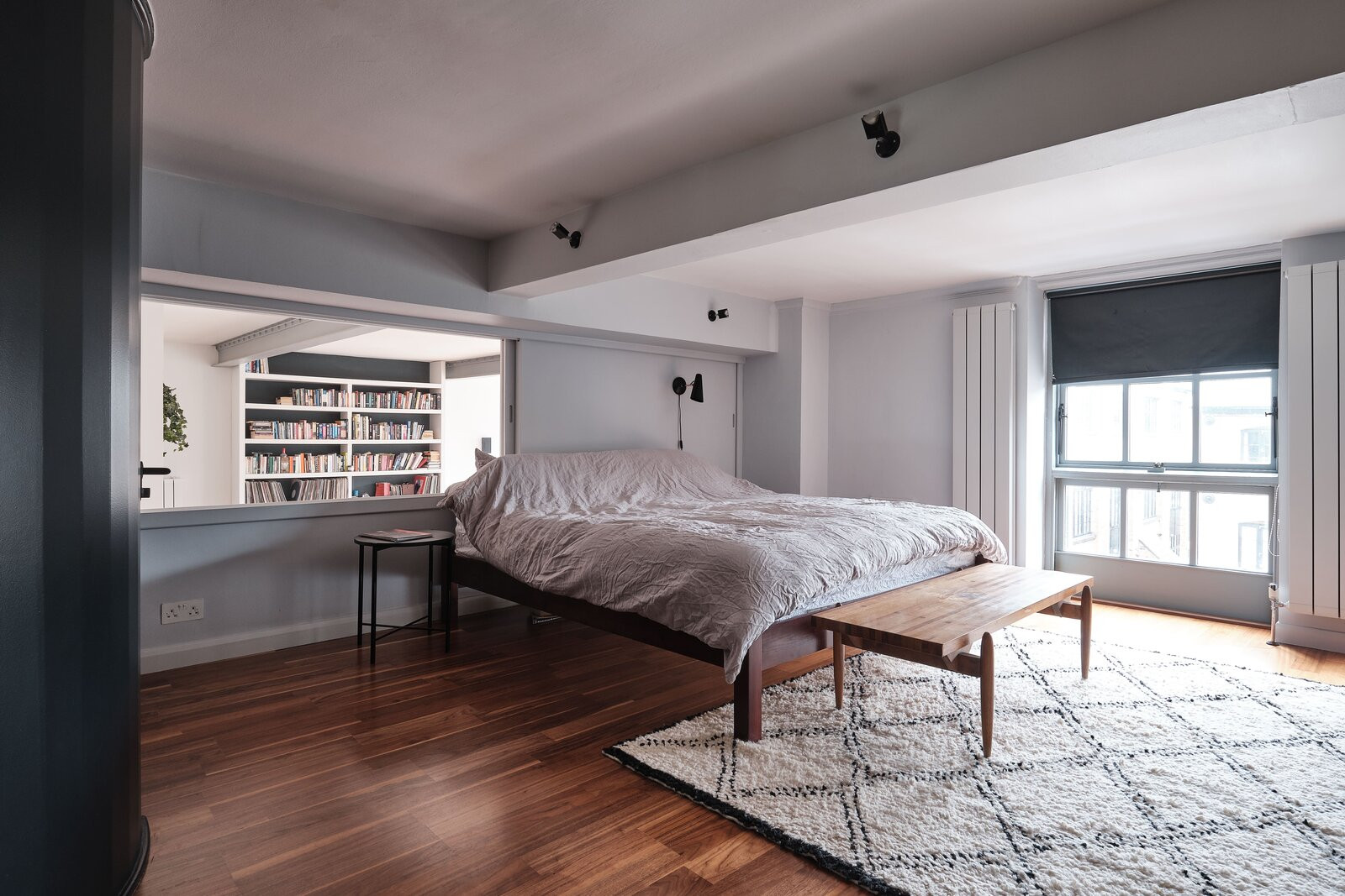 Bedroom, Bed, Wall Lighting, Dark Hardwood Floor, Bench, and Night Stands Upstairs, a movable wall partition opens the principal suite to the living area below.  Photo 9 of 13 in For £1.2M, Snag This Spacious London Flat Inside a Converted Victorian Schoolhouse
