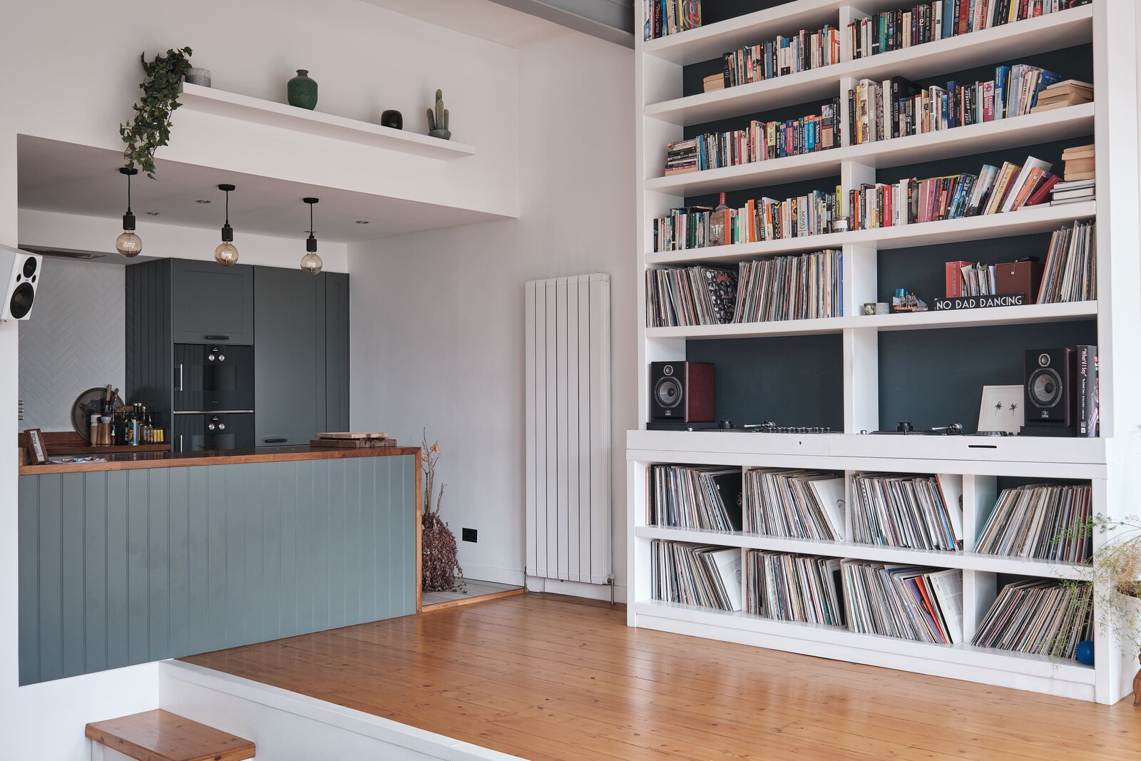 Living Room and Bookcase A upgraded kitchen occupies a cozy alcove opposite the bookcase and opens to the rest of the room. Contrasting, handmade cabinetry fill the space.  Photo 3 of 13 in For £1.2M, Snag This Spacious London Flat Inside a Converted Victorian Schoolhouse